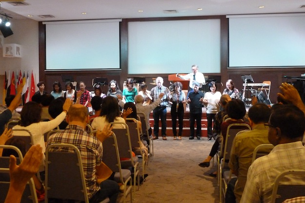 Congregation praying for the missionary team of the church
