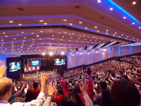 The congregation lifting their hands in prayer