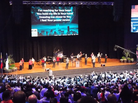 The attendees coming to the front of the stage for prayer