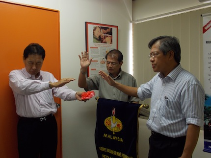 Dr Lim Chei Seng with brother Victor Liew and brother David praying for the attendees