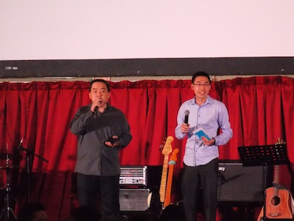 Pr Shawn Kong (right) making church announcements on-stage