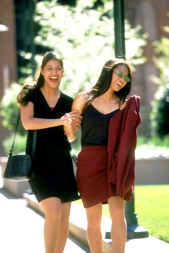 Latino and Asian women friends walking and laughing together.