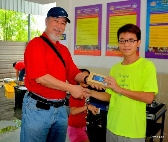 Rev David Loo presenting the prize to the winner of Samsung Phone Raffles