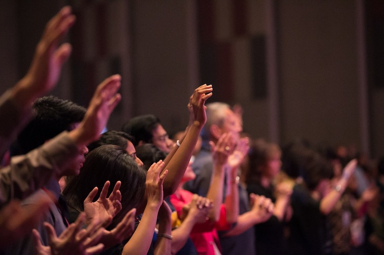 The audience lifting their hands in worship