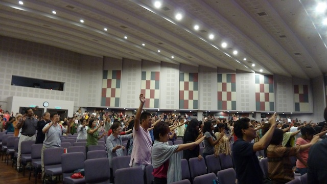 The congregation lifting their hands in prayer for Datuk Paul Low