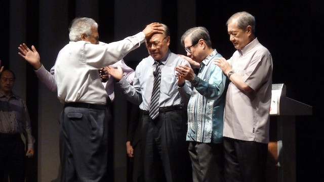 Rev Henry Pillai laying his hands to pray for Datuk Paul Low