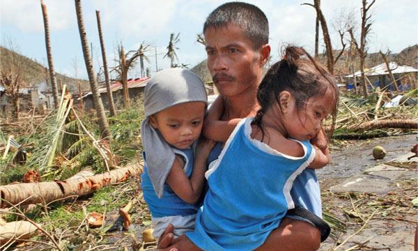 Survivor of Typhoon Haiyan, holding his children