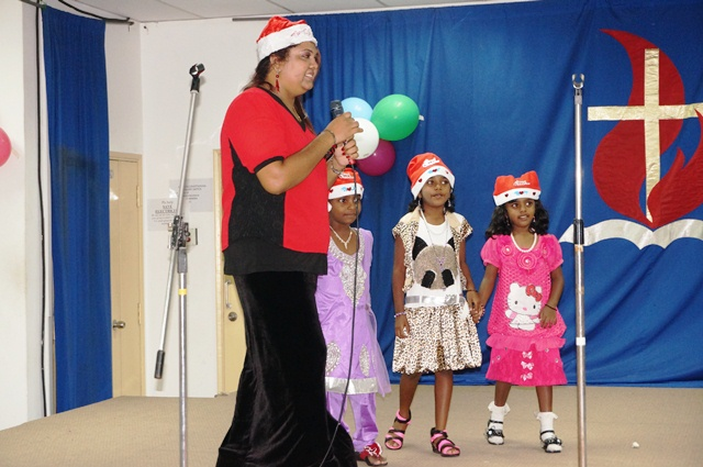 Sheila, emcee for the night with the children performing the Santa Claus dance on-stage