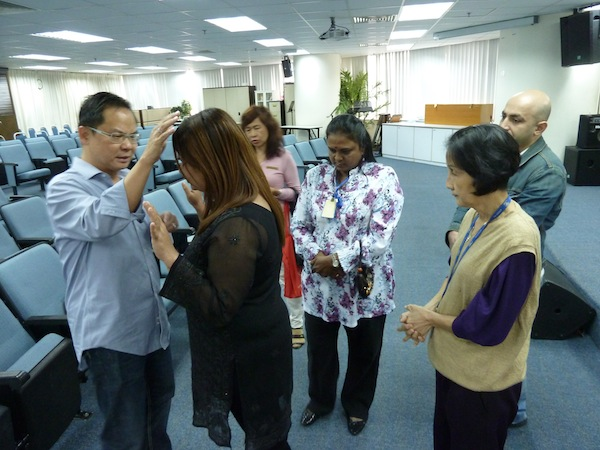 Eddy Yong praying for God to heal the people