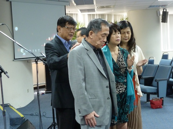 Pr Peter Sze and wife See Fen praying for Datuk Tony Tiah and wife Datin Alicia