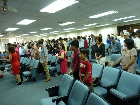 The attendees raising their hands in prayer for Datuk Tony Tiah and Datin Alicia