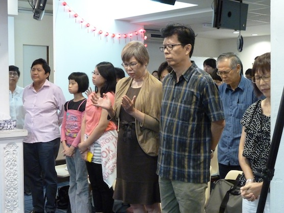 The congregation of Christian Charis Centre bowing their heads in prayer