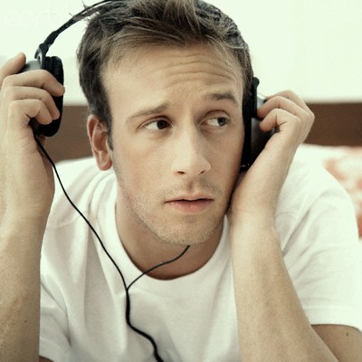 Man Listening to Headphones --- Image by © Flint/Corbis