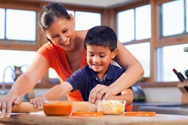 Mixed race mother and son cooking together