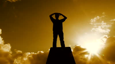 stock-footage-beautiful-warm-cloudscape-with-man-silhouetted-standing-atop-pedestal-structure-looking-out-among