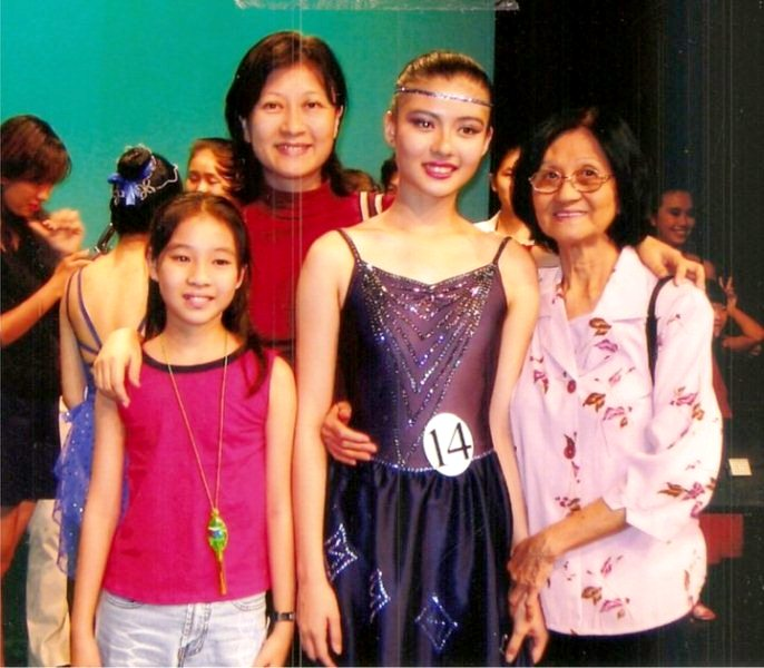 Carey Ng posing her mother, younger sister, and grandmother as a gymnast