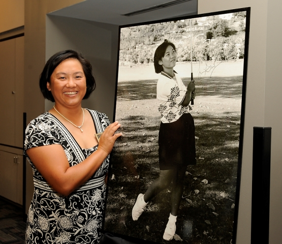 Siew Ai standing beside a picture of her during her collegiate golf career