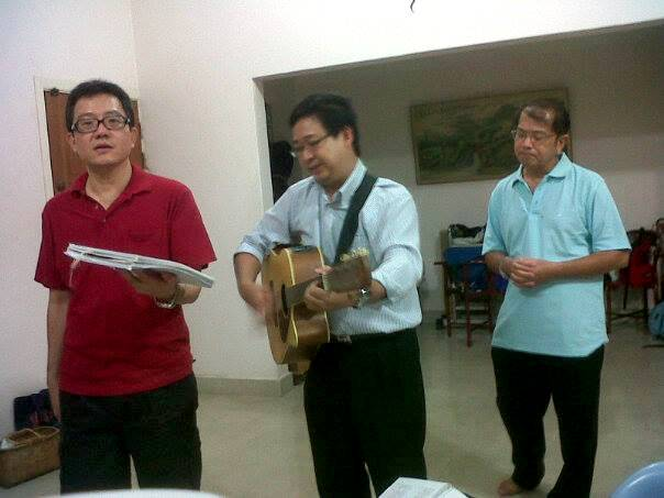 Husband of Sis Jin Mei playing the guitar for cell group with her father (far right)