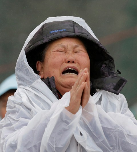 A relative of a missing passenger aboard the sunken ferry Sewol of South Korea prays while crying at a port