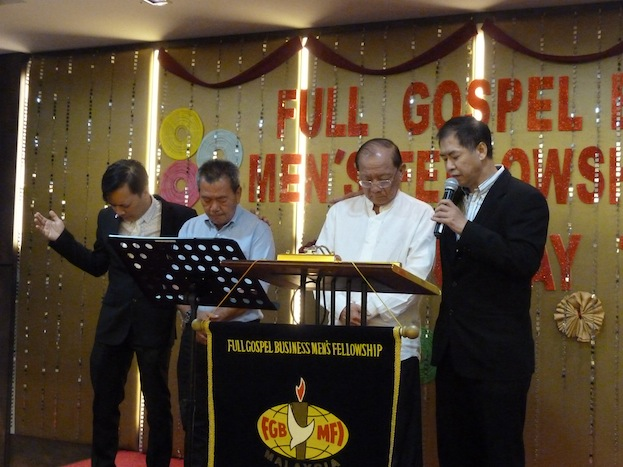 Datuk Johnny Mun (2nd from left) and Tan Koon Swan (3rd from left) being prayed for