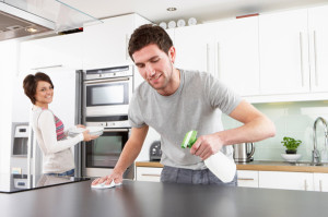 young-happy-man-helping-smiling-wife-clean-kitchen