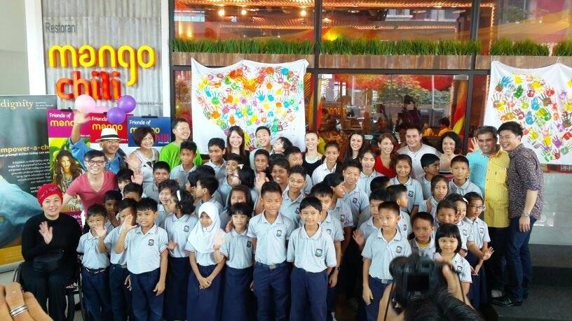 Dignity for Children kids, beneficiaries for the Food for Good program, standing in front of their masterpiece - 2 original heart shape art pieces made their handprints using PELAKA paint
