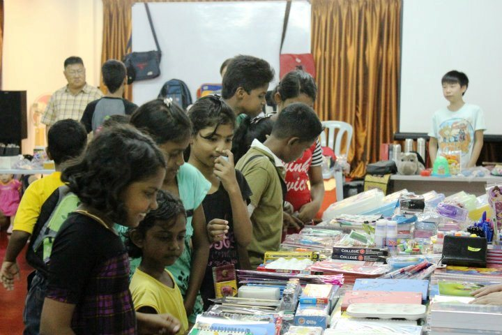 Children huddling together at the Coupon Exchange booth, excited to exchange for items