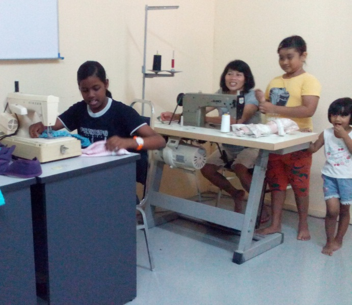 Children learning how to sew with donated sewing machines