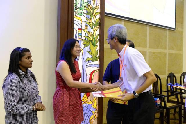 Wong Young Soon presenting Kursus Kewangan Komuniti to Amelia Leong from World Vision Malaysia