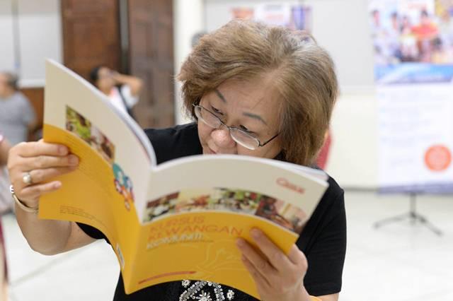 An attendee reading the Kursus Kewangan Komuniti
