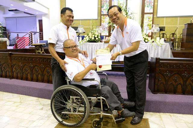 Dr David Wong, Chairman of Malaysian CARE, handing Yap Khen Siong a 20-year-award