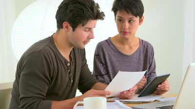 stock-footage-mixed-race-couple-looking-over-finances