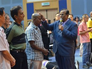 Dr Ananda Sitra praying for the attendees at his last visit in Glad Tidings Petaling Jaya