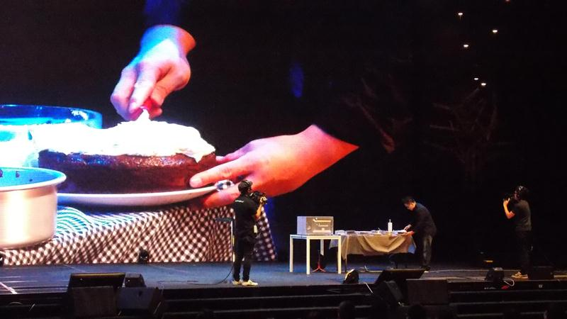 Rev Wayne making a delicious looking cake on stage to illustrate his message because different people are made differently