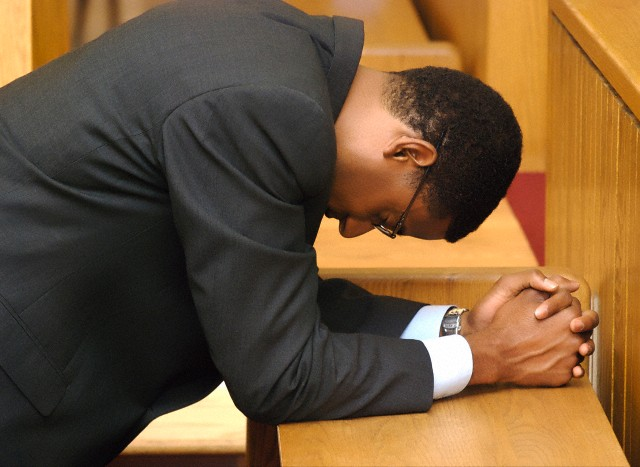 Side profile of a businessman praying