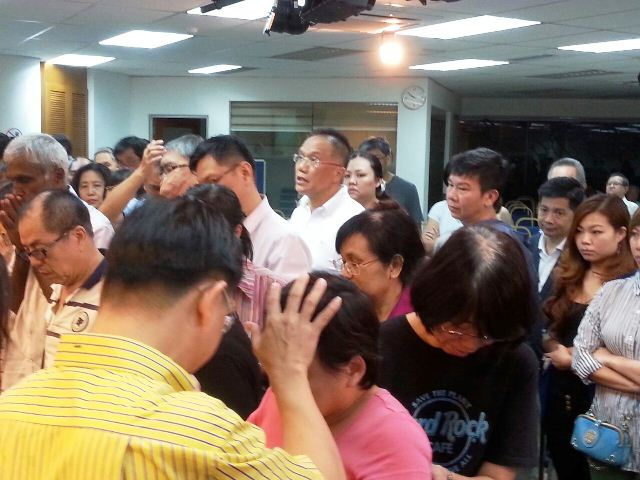 Eddy Yong praying for an attendee