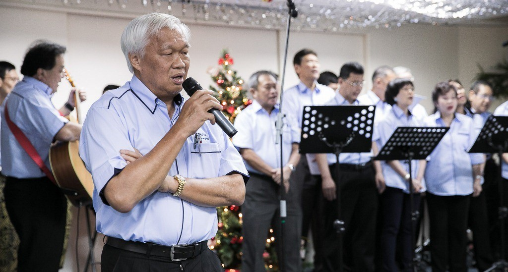 Tan Sri Chan Ah Chye sharing God's goodness, accompanied by the choir from Talam Transform Bhd