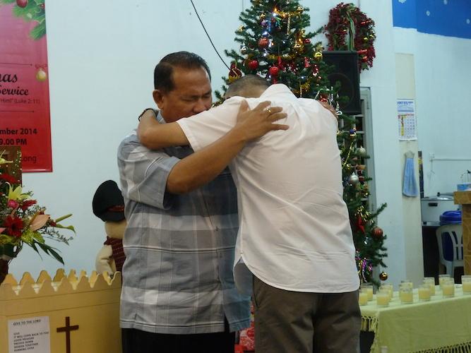 Pastor Joshua Low praying for Pastor Tan Jooi Long