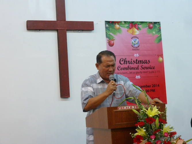 Pastor Joshua Low of the Hosannah Praise Assembly praying for the congregation before the Christmas dinner