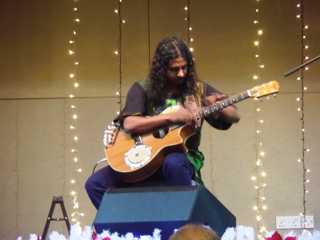 Benny Prasad performing on the Bentar III bongo guitar, an instrument created by him.