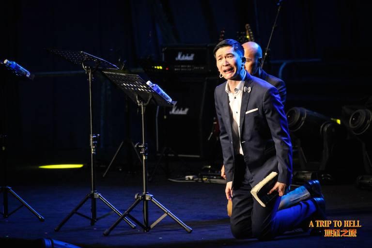 Rev Philip Mantofa kneeling onstage