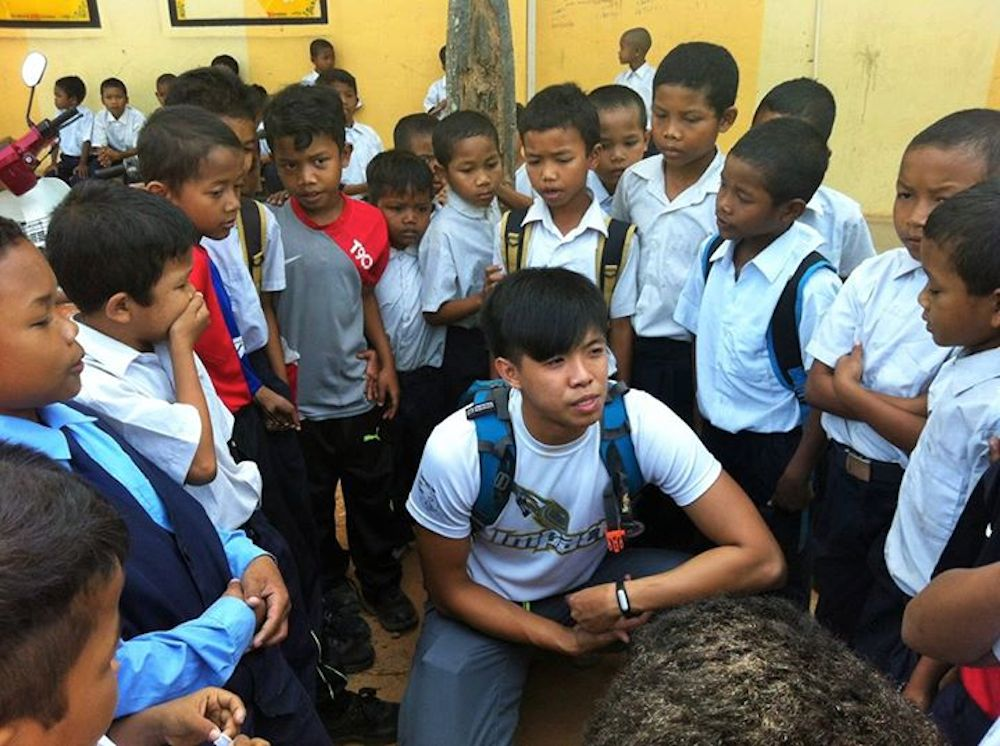 Volunteer Jansen Yeoh being surrounded by the Temiars children in Kuala Betis