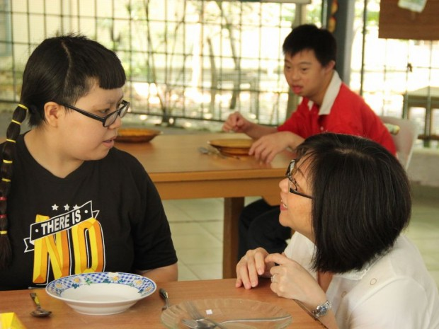 Mrs. Yammy Ang, an advisor for Wings Melaka, interacting with a young adult