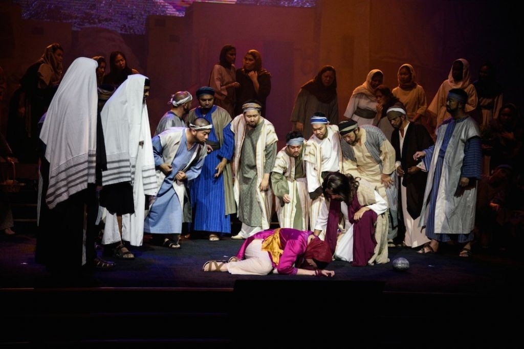 A scene where the religious teachers of law gathered together to stone the adulterous woman, but redeemed by Jesus