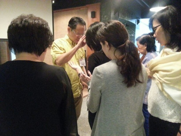 Eddy Yong praying for Jesus' mighty power of healing to come upon the people