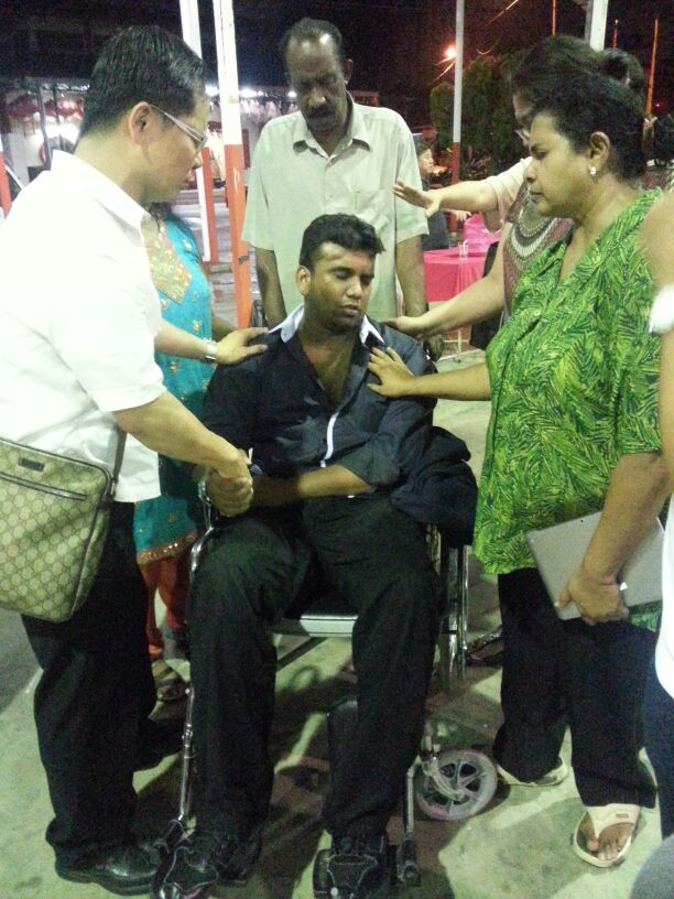 Eddy Yong praying for a brother on a wheelchair
