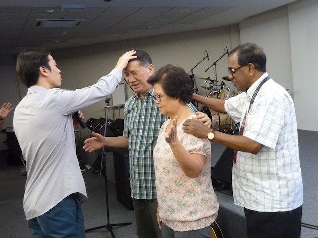 Pr Steve laying hands to pray for the founding team of NLCC with Pr Dennis Balan