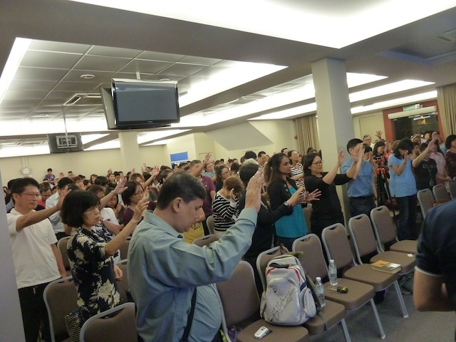 The congregation raising their hands in prayer