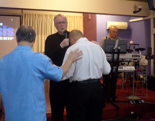 Pastor Colin praying for the church members