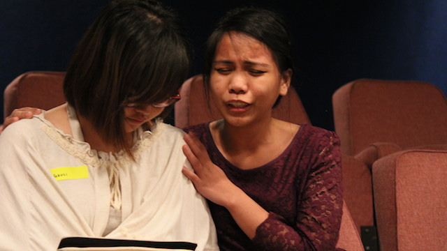 A sister-in-Christ praying for healing for an attendee in the healing crusade